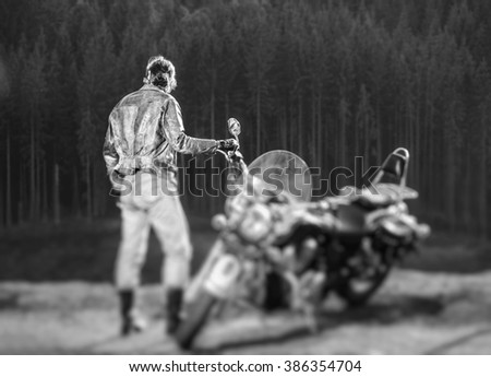 Long haired biker standing near his custom made cruiser motorcycle, wearing leather jacket and jeans. Looking into distance. Shot from the back. Tilt lens blur effect. black and white - stock photo