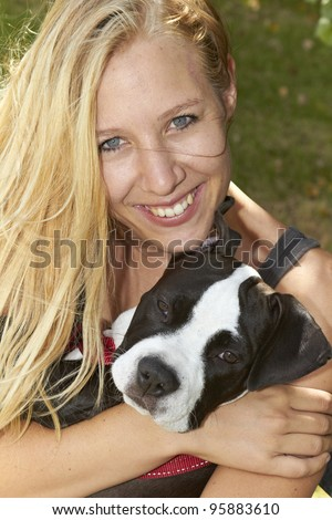 Long haired blond embracing her Pit Bull puppy