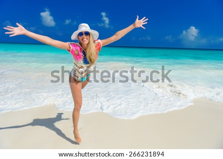 long haired blonde woman with flower in hair in bikini on tropical beach - stock photo