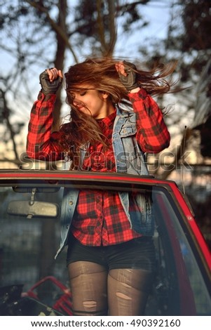 long-haired brunette girl dancing in a car
