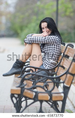 Long-haired brunette in shorts siting on bench in park. She laughing and hides her mouth
