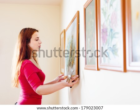 Long-haired girl hanging  pictures in frames on wall