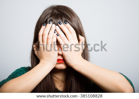 long-haired girl hides her face in her hands, a student in isolation on a gray background - stock photo