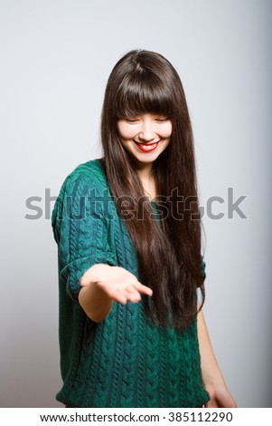 long-haired girl holding something invisible on the palms, business woman isolated on a gray background - stock photo