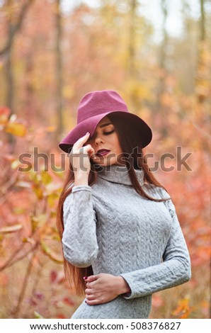 Long-haired girl in a burgundy hat in the middle of autumn forest
