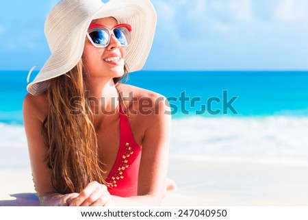 long haired girl in bikini and straw hat on tropical caribbean beach