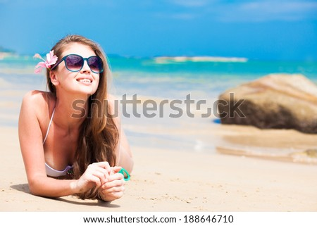 long haired girl in bikini and sunglasses on tropical beach - stock photo