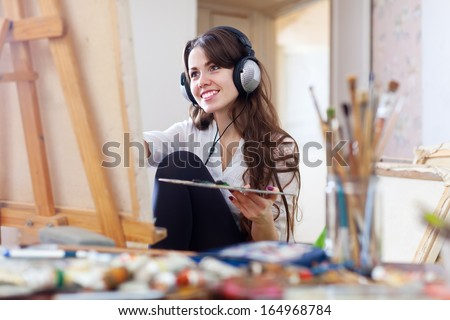 Long-haired girl in headphones  paints with oil colors  on canvas - stock photo