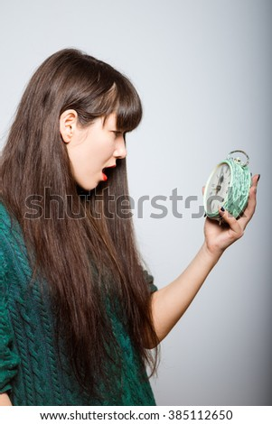 long-haired girl looks shocked at the alarm clock, business woman isolated on a gray background - stock photo