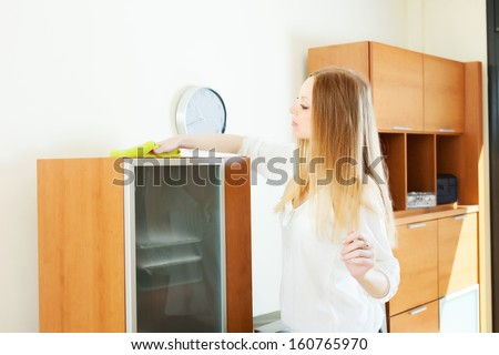 long-haired housewife cleaning furniture at home