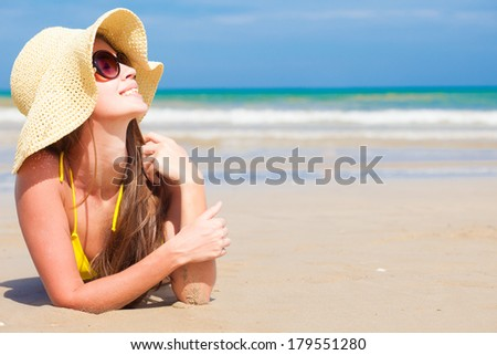 long haired woman in bikini and straw hat on tropical beach