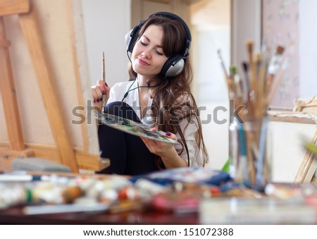 Long-haired woman in headphones  paints with oil colors and brushes on canvas in workshop interior - stock photo