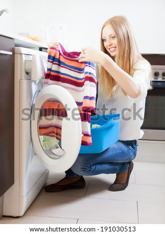 Long-haired woman with clothes near washing machine at  home