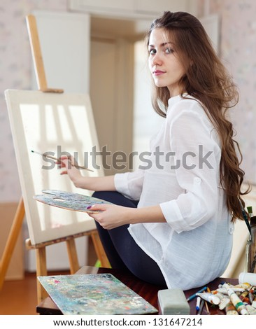 Long-haired woman with oil colors and brushes near easel with blank canvas ready for job  in workshop - stock photo