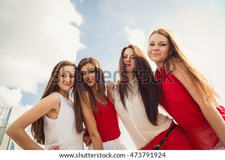Long-haired women lean to each other while posing under bright blue sky