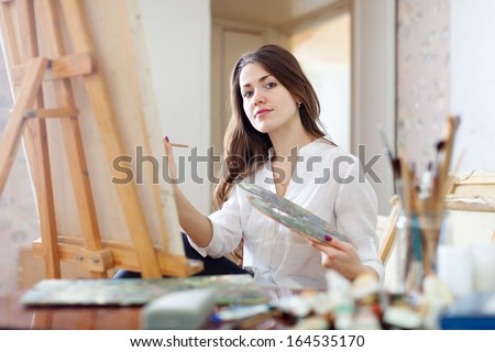 Long-haired young woman paints on canvas in workshop - stock photo