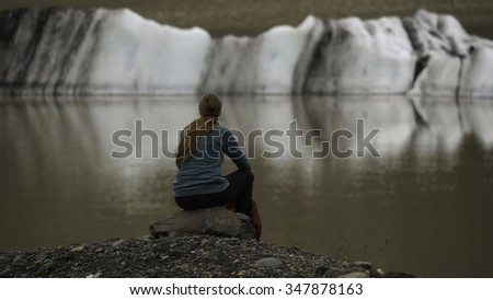 Long haired young women from behind looking across water at an iceberg