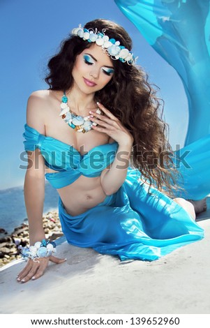 Long Healthy Hair. Beautiful brunette woman in blue silk luxury dress with sea jewelry. - stock photo