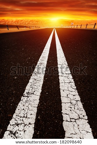 Long highway, road on sunset, red dramatic cloudy sky, two white line on dark asphalt, speed highway along desert,  freedom and travel concept - stock photo