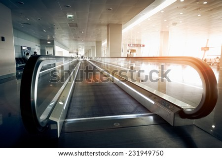 Long horizontal escalator at modern airport terminal at sun light - stock photo