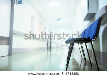 Long hospital hallway with vacant chairs.