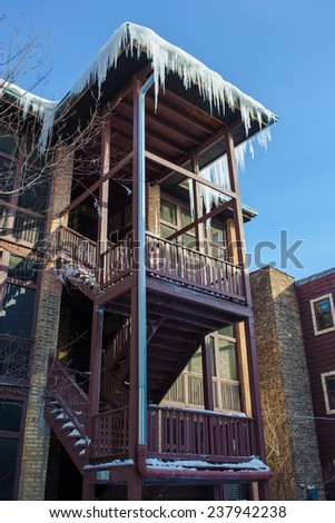 Long icicles hanging from a apartment building roof - stock photo