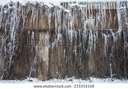 Long Icicles Hanging from Roof down to Wall