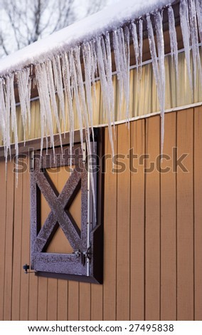 Long icicles hanging from the side of an orange barn. - stock photo