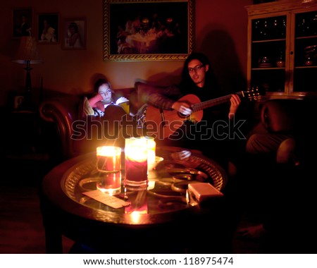 LONG ISLAND, NY- OCT 31: Couple in candlelit home due to Hurricane Sandy massive power outage in New York on Oct 31, 2012.  Sandy struck NY on Oct 29 leaving 1 million Long Islanders without power. - stock photo