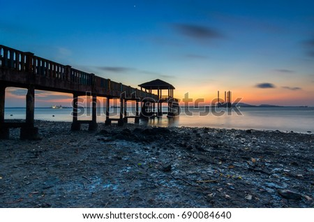 Long jetty during sunrise. Motion blur at the sky and ocean (Image has certain noise and soft focus due to long exposure)