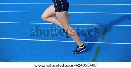 long legs of young female runner running on athletic track with blue colored lanes
