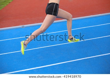 long legs of young runner running on athletic track with blue colored lanes