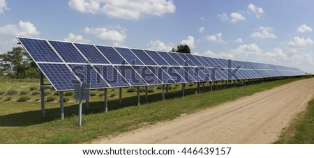 Long line of no name solar electric generation panels is near the rural road. Panoramic collage from several photos