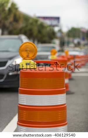 long line of orange traffic barrier barrels to detour traffic around construction zone shallow depth of field vertical - stock photo