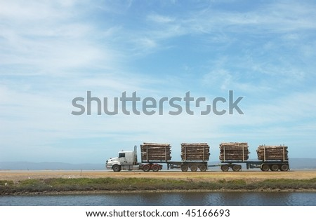 Long logging truck with clear sky - stock photo