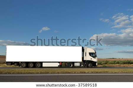 Long lorry with white truck and trailer on highway against blue sky. See my other best vans collection.