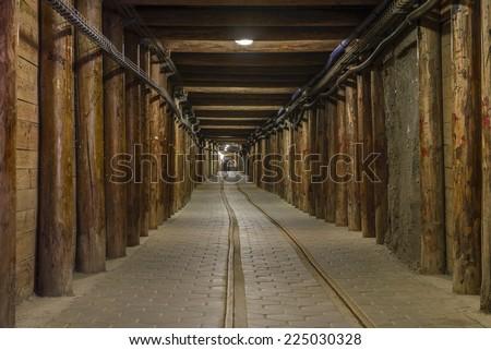 Long mineshaft hallway with wood support beams and railroad tracks. Wieliczka Salt Mine - Krak�³w, Poland. - stock photo