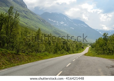 long narrow mountain road going through the arctic summer mountain and valley landscape