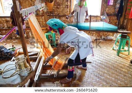 Long necked Kayan Padaung woman weaving on a loom,  Inle Lake,  Myanmar (Burma) - stock photo