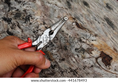 Long nose pliers on wood grain background.