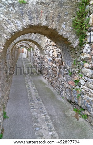 Long passage under stone arches from the old town of Villefranche de Conflent in the Conflent region of Catalonia, Pyrenees-Orientales department, France - stock photo