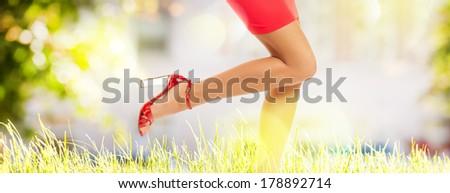 Long perfect female legs wearing high heels on summer grass - stock photo