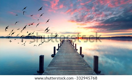 long pier leading out onto the lake, sunrise on lake, long way out with fog - stock photo