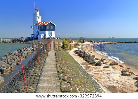 Long pier leading to distant lighthouse in Marken, Netherlands  - stock photo