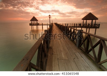 Long pier overlooking the sea during sunrise. - stock photo