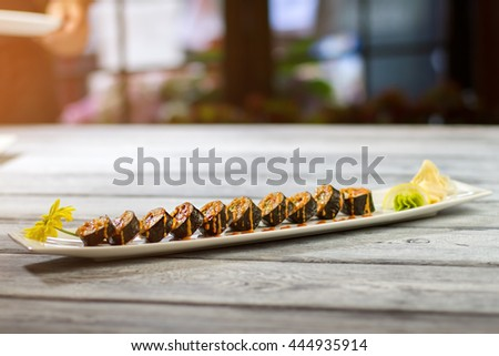 Long plate with sushi rolls. Sushi plate on wooden surface. Delicious low-calorie food. Hosomaki rolls and marinated ginger. - stock photo