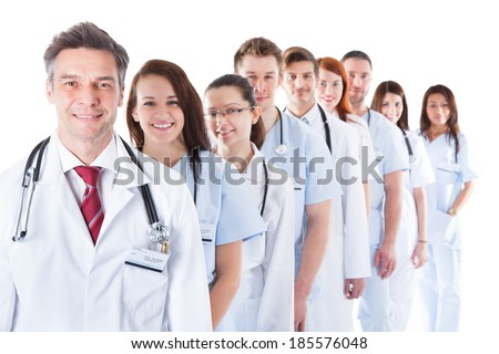 Long receding line or queue of smiling doctors and nurses in white uniforms wearing stethoscopes around their necks isolated on white - stock photo