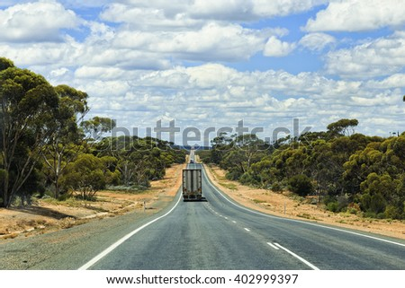 Long remote eyre highway in Nullarbor plain of Western Australia with lonely road train truck and tourist caravan van between eucalyptus woods.