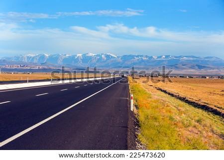 Long road against Toros mountain - stock photo