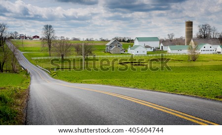Long road beside an Amish farm. - stock photo